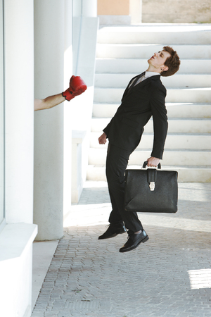 knocked out: Young businessman gets knocked out by a punch, business failure concept
