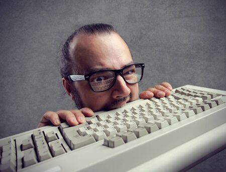 eccentric: Eccentric angry man bites a keyboard Stock Photo