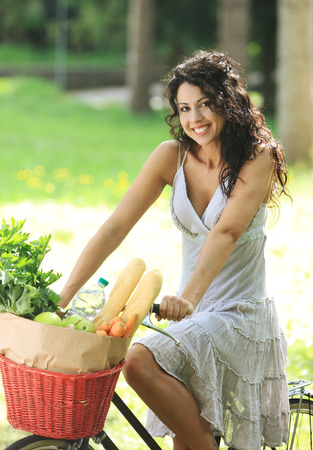 Portrait of a beautiful young woman riding bicycle with groceries in basket photo