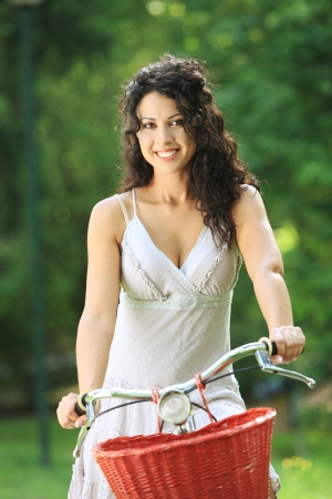 Portrait of pretty young woman with bicycle in a park smiling photo