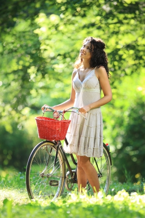 Smiling girl looking around while walking with her bicycle at park photo