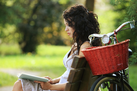 Young woman reading a book at a park photo