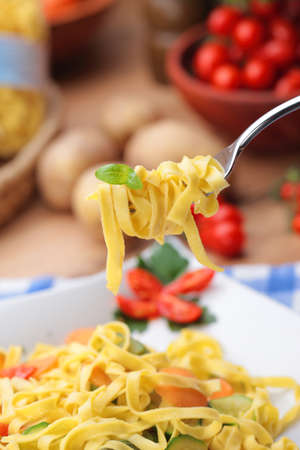 Fork holds tagliatelle with some basil leaves
