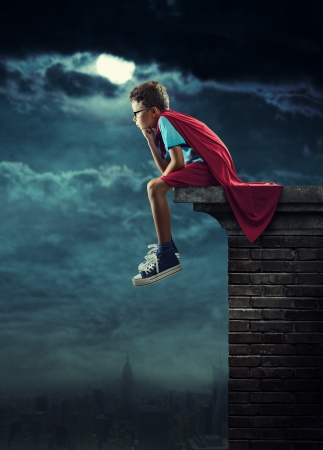 conceptual cute: A young boy dreams of becoming a superhero. Stock Photo