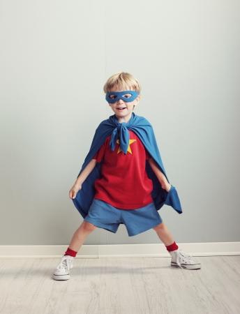 ni�os rubios: Un muchacho joven sue�a con ser un superh�roe.