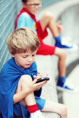 crime fighter: A child superhero playing with a smartphone