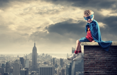 superhero cape: A young boy dreams of becoming a superhero. Stock Photo