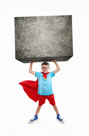 Little boy lifting a large rock with hands Stock Photo