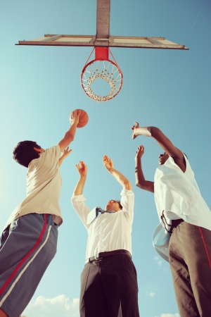 basketball hoop: Two Afro-American boy and a man playing basketball against blue sky Stock Photo