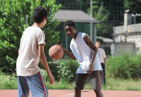 Two young African boy play basketball,  photo