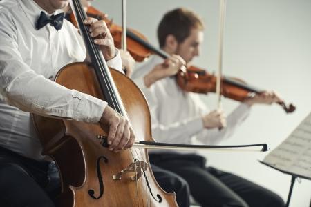 orquesta: Violonchelista y violinista tocando en el concierto Foto de archivo