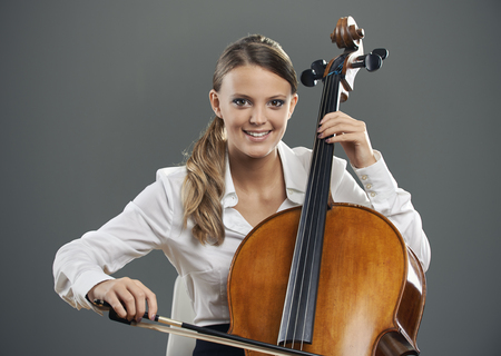 cellist: Smiling young woman cellist on grey background