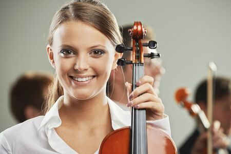 woman violin: Portrait of a beautiful female violinist, musicians on background
