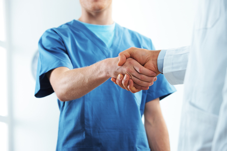 congratulating: Two medical people handshaking at office  Stock Photo