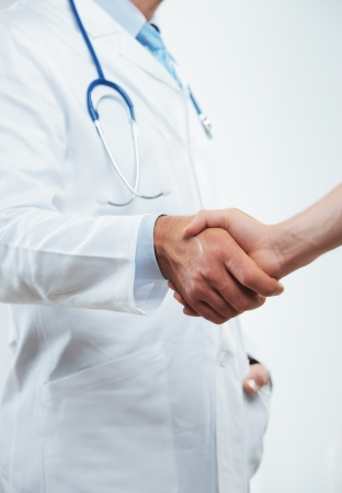 Cropped shot of a doctor handshaking with patient photo