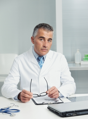 Mature male doctor sitting at desk in doctors room photo