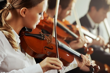 Violinists playing at the concert, young beautiful woman on foreground photo