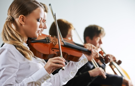 Musicians in concert, beautiful female violinist on foreground photo