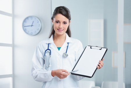 Confident woman doctor pointing at the clipboard photo