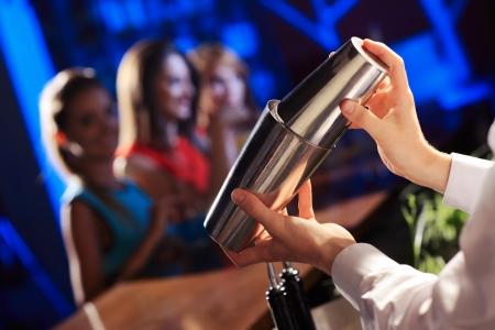 Barman schudden van een cocktail, jonge vrouwen op de achtergrond