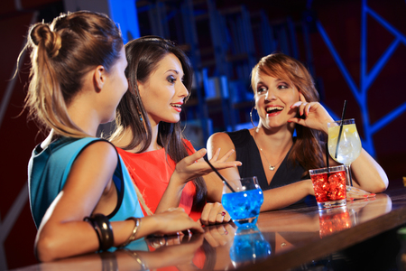 Three young women having a drink and talking in a night club  photo