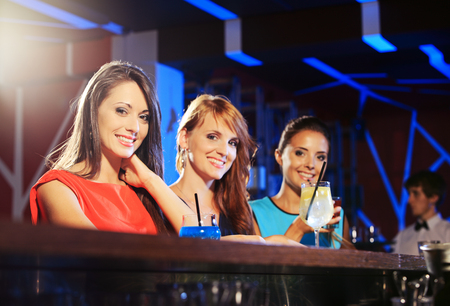 Three young women having a drink in a night club  photo