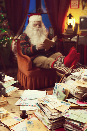 messy desk: The messy desk of Santa Claus, he reading a book on background