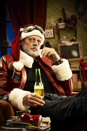 A Cheerful Bad Santa drinking beer and smoking cigarette Stock Photo - 23731397
