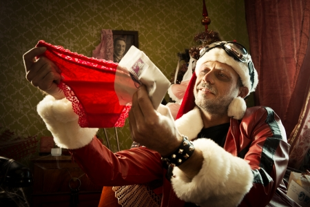 A cheerful Bad Santa holding a red panties photo