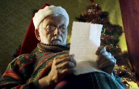 Portrait of a Father Christmas looking letters sent to him by children. Stock Photo - 23731465