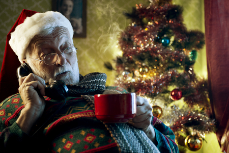 Pictures of Santa Claus relaxing at home and talking on phone photo