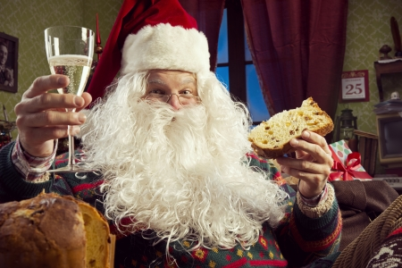 Portrait of Santa Claus celebrating with a glass of champagne and panettone