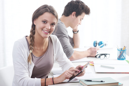 Teen boy and girl sitting together and studying  photo