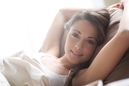 Young woman lying in bed and smiling at the camera  photo