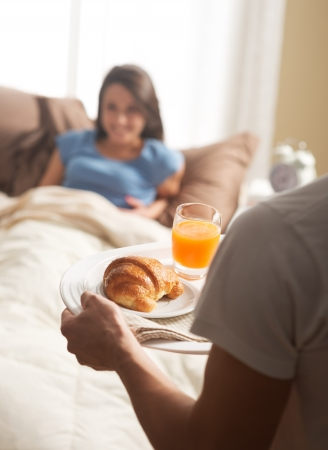Hand holding breakfast tray to a happy relaxed woman in bed  photo