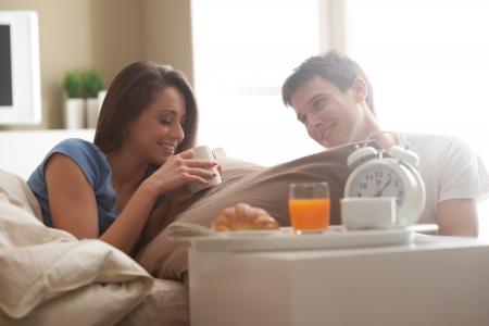 enamorados en la cama: Hermosa joven sonriente pareja de desayunar en la cama Foto de archivo