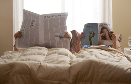 Young couple in bedroom reading newspaper and magazine photo