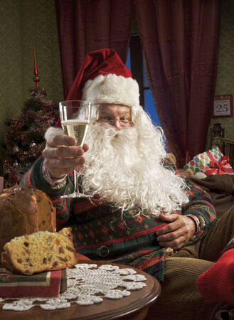Portrait of Santa Claus celebrating with a glass of champagne photo