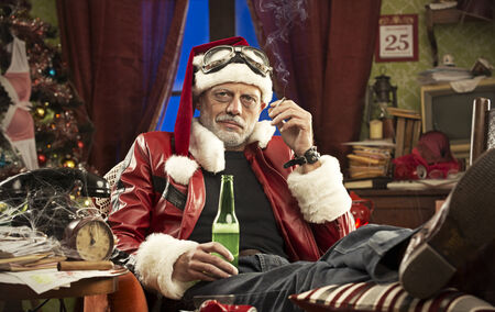 A Cheerful Bad Santa drinking beer and smoking cigarette photo