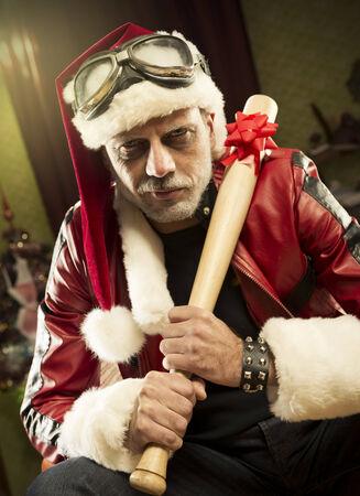 expressing negativity: A frowning Bad Santa with baseball bat looking at camera Stock Photo