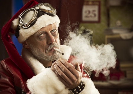 unhealthy living: Portrait of a frowning Bad Santa smoking a joint