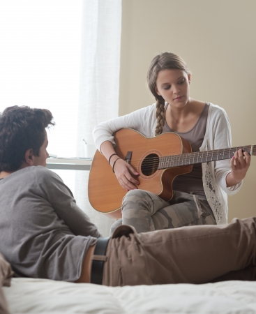 Beautiful girl playing guitar for her boyfriend at home  photo