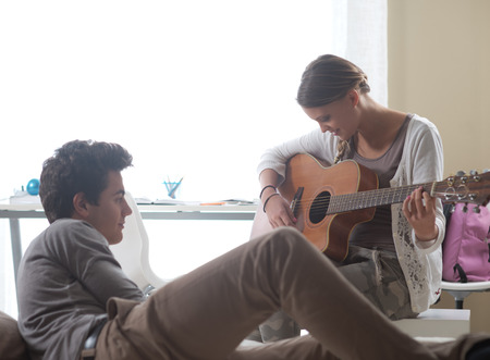 teen couple: Beautiful girl playing guitar for her boyfriend at home
