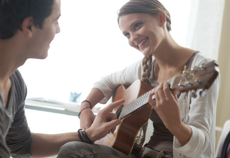 music education: Young beautiful couple resting at home and playing guitar