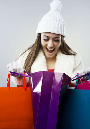 Young happy woman opening a shopping bag photo