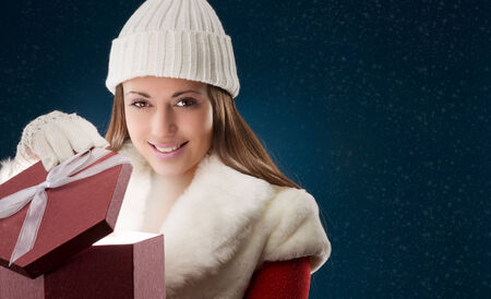 Happy young woman opening Christmas presents, copy space photo
