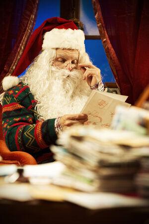 Portrait of Santa Claus reading a Christmas letter photo