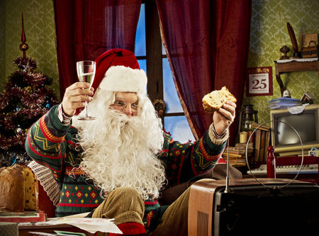 Portrait of Santa Claus watching tv, celebrating with a glass of champagne and panettone Editorial
