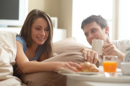 desayuno romantico: Hermosa joven sonriente pareja de desayunar en la cama Foto de archivo