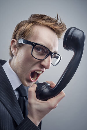 Angry nerd businessman retro telephone call shouting photo